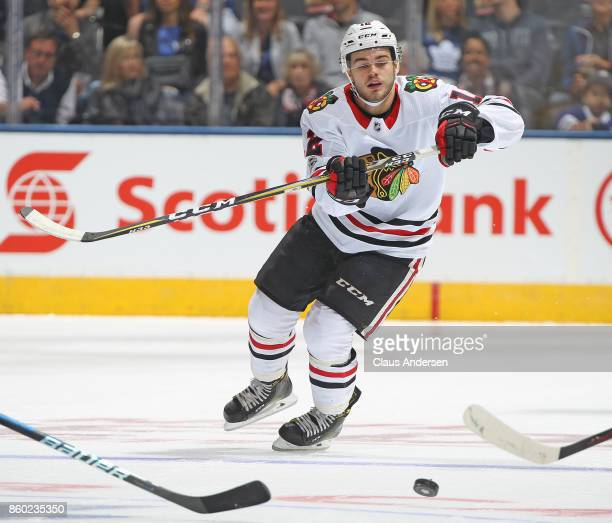 Alex DeBrincat of the Chicago Blackhawks skates after a puck against the Toronto Maple Leafs in an NHL game at the Air Canada Centre on October 9...