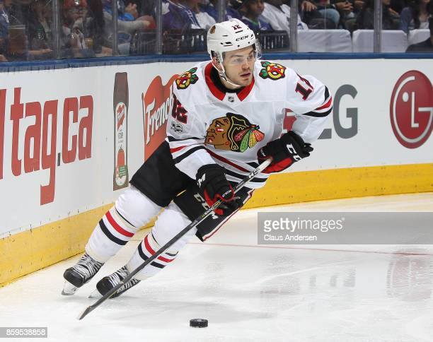 Alex DeBrincat of the Chicago Blackhawks skates with the puck against the Toronto Maple Leafs in an NHL game at the Air Canada Centre on October 9...
