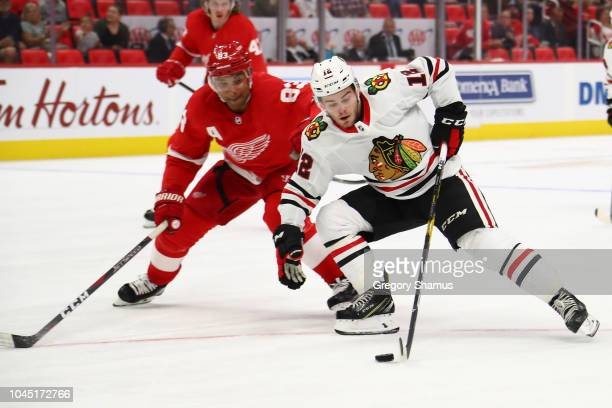Alex DeBrincat of the Chicago Blackhawks tires to get around Trevor Daley of the Detroit Red Wings during a pre season game at Little Caesars Arena...