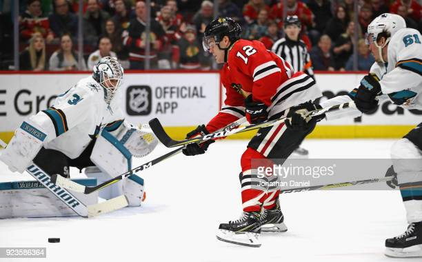 Alex DeBrincat of the Chicago Blackhawks tries to get off a shot at Martin Jones of the San Jose Sharks pressured by Justin Braun at the United...