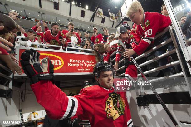 Alex DeBrincat of the Chicago Blackhawks walks out to the ice prior to the game against the Dallas Stars at the United Center on November 30 2017 in...