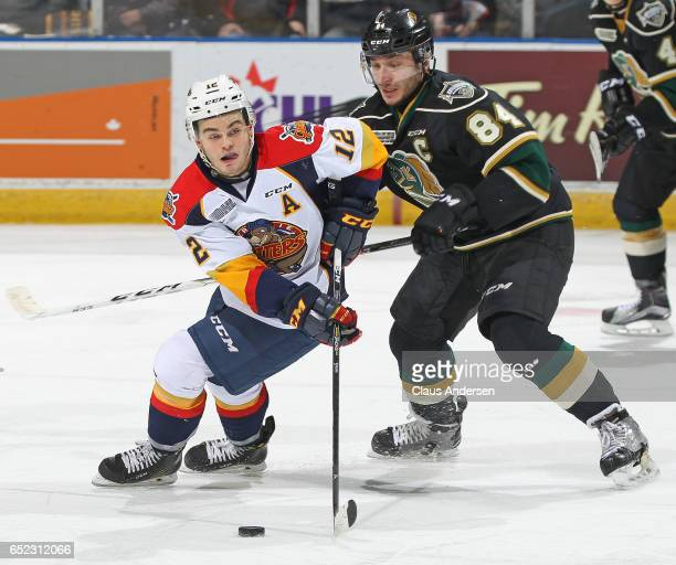 Alex DeBrincat of the Erie Otters skates with the puck against a checking JJ Piccinich of the London Knights during an OHL game at Budweiser Gardens...