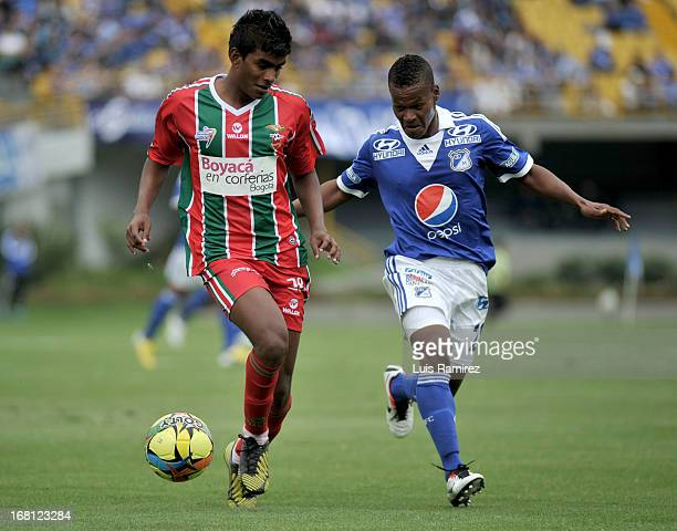 Alex Diaz of Millonarios fights for the ball with Julian Barahona of Patriotas during a match between Millonarios and Patriotas as part of Liga...