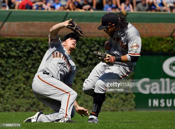 Alex Dickerson of the San Francisco Giants avoids colliding into Brandon Crawford of the San Francisco Giants while making the catch in the fifth...