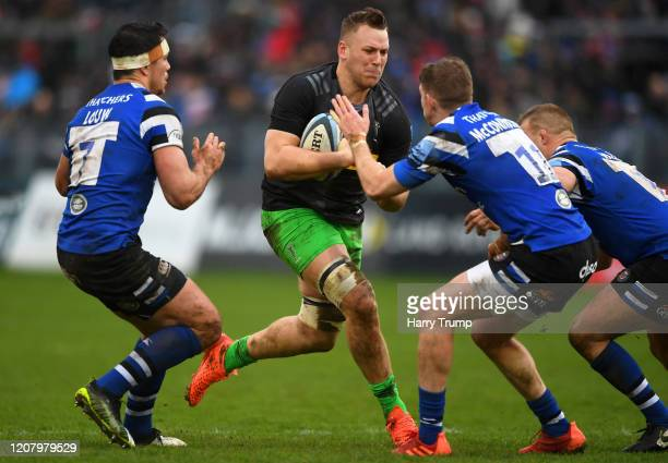 Alex Dombrandt of Harlequins looks to break past the tackle from Francois Louw of Bath Rugby and Ruaridh McConnochie of Bath Rugby during the...