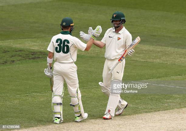 Alex Doolan of Tasmania celebrates with Tim Paine after scoring his double century during day three of the Sheffield Shield match between Victoria...