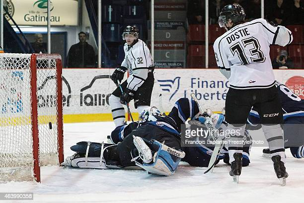 Alex Dostie of the Gatineau Olympiques looks on as teammate Yakov Trenin scores his second period goal against the Chicoutimi Sagueneens on February...