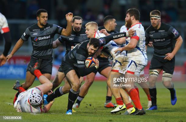 Alex Dunbar of Newcastle Falcons is tackled by Arron Reed of Sale Sharks during the Premiership Rugby Cup match between Sale Sharks and Newcastle...