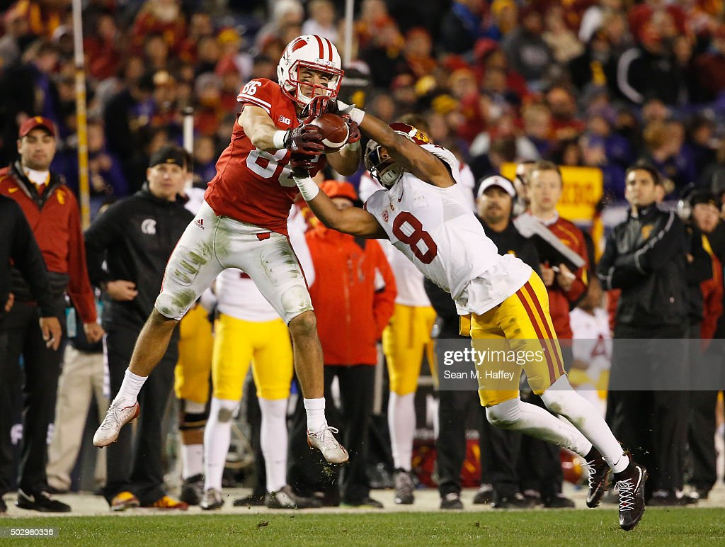 Alex Erickson #86 of the Wisconsin Badgers battles for a pass against Iman Marshall #8 of the USC Trojans during the second half of the National University Holiday Bowl at Qualcomm Stadium on December 30, 2015 in San Diego, California.
