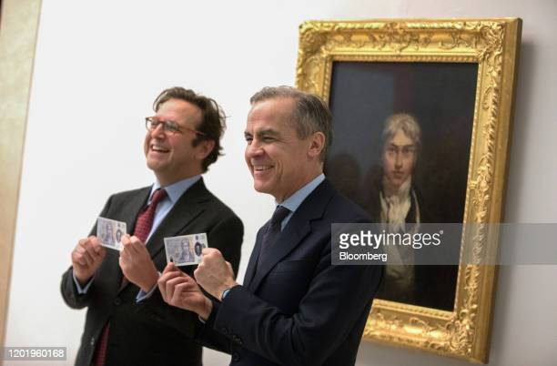 Alex Farquharson director of Tate Britain left and Mark Carney governor of the Bank of England hold a new 20pound banknote in front of JMW Turner's...
