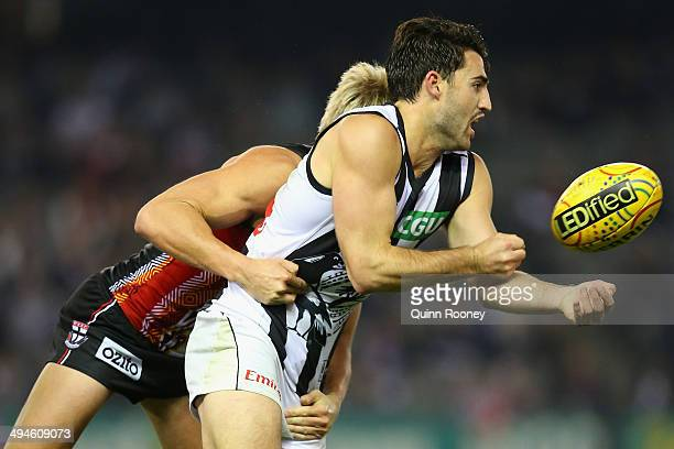 Alex Fasolo of the Magpies handballs whilst being tackled by Clinton Jones of the Saints during the round 11 AFL match between the St Kilda Saints...