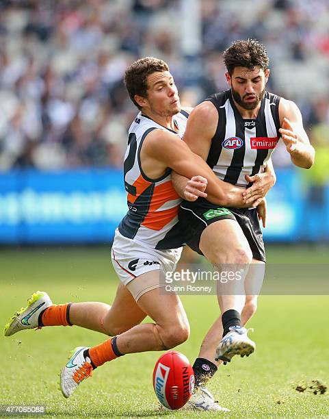 Alex Fasolo of the Magpies kicks whilst being tackled by Josh Kelly of the Giants during the round 11 AFL match between the Collingwood Magpies and...