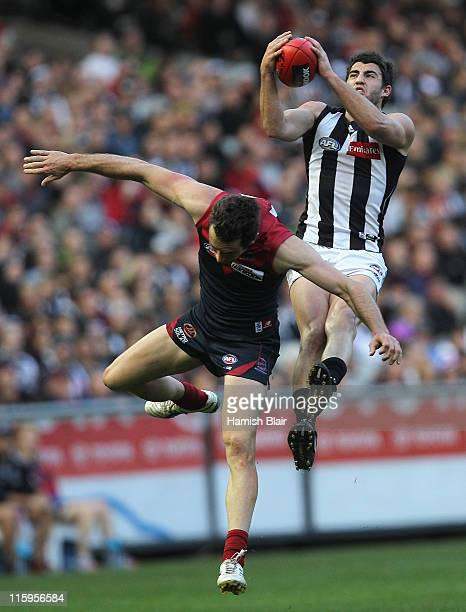 Alex Fasolo of the Magpies marks over Joel MacDonald of the Demons during the round 12 AFL match between the Melbourne Demons and the Collingwood...