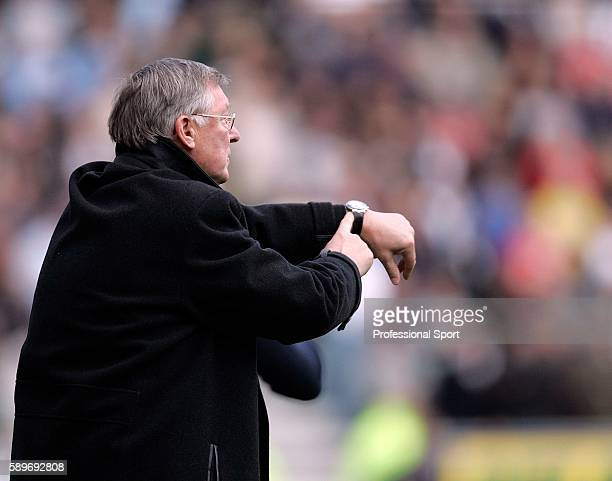 Alex Ferguson manager of Manchester United points to his watch during the Barclays Premiership match between Wigan Athletic and Manchester United at...
