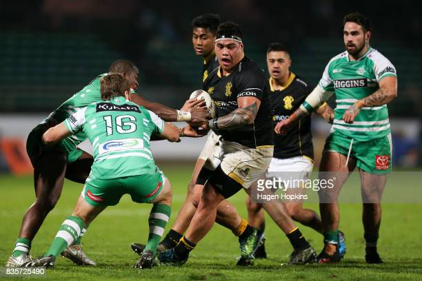 Alex Fidow of Wellington looks to evade the tackles of Willy Ambaka and Tim Cadwallader of Manawatu during the round one Mitre 10 Cup match between...