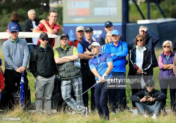 Alex Fitzpatrick of the Great Britain and Ireland team plays his third shot on the 15th hole watched closely by his brother European Tour star...