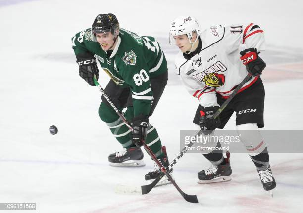 Alex Formenton of the London Knights and Daylon Groulx of the Owen Sound Attack compete for control of the puck in the second period during OHL game...