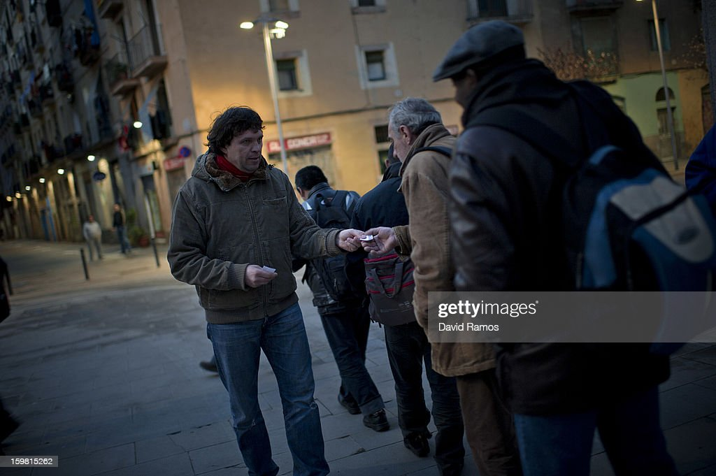 Alex from Moldova gives out tickets to needy people for the firsts turn of the breakfast before opening 'El Chiringuito de Dios' ('the Stall of God') on January 3, 2013 in Barcelona, Spain. The German pastor Wolfgang Striebinger has lived in Barcelona since 1991, originally employed to minister to youths during the Barcelona Olympic Games, he decided to stay and since 2000 has run 'El Chinguito de Dios' (The Stall of God). In his mission to support the homeless, Wolfgang and his volunteers offer a place for up to 200 people to come and have some food daily and also offering them assistance with grooming and clothes. Many of the volunteers are homeless and help out in return for meals and a bed. Wolfgang's ethos is to provide peace, calm and dignity to all those that need it amongst Barcelona's burgeoning homeless population. Due to the economic situation his doors are now also open to the long term unemployed and families with little or no income. According to the latest figures 21.8% of the Spanish populations are living below the poverty line.