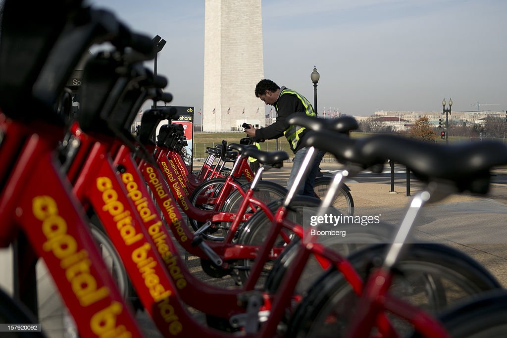 Alex Fuentes removes a Capital Bikeshare bicycle from a docking station in Washington, D.C., U.S., on Friday, Nov. 30, 2012. Since Sept. 2010, Capital Bikeshare has dispersed more than 1700 bikes for rent across the city and has totaled over 3.5 million rides since Sept. 2011. Alta Bicycle Share, the company that was awarded the contract to run the program, has installed 191 solar-powered docking stations throughout the District and Arlington, Virginia. Photographer: Andrew Harrer/Bloomberg via Getty Images