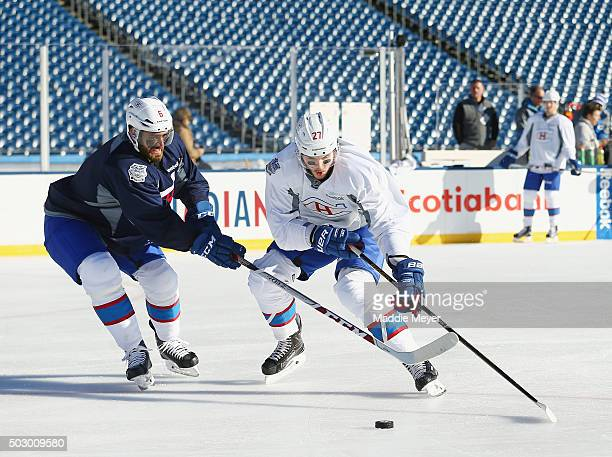 Alex Galchenyuk moves the puck around Greg Pateryn of the Montreal Canadiens during practice at Gillette Stadium on December 31 2015 in Foxboro...