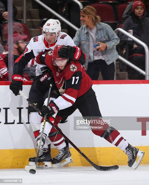 Alex Galchenyuk of the Arizona Coyotes attempts to control the puck under pressure from Alex Formenton of the Ottawa Senators during the second...