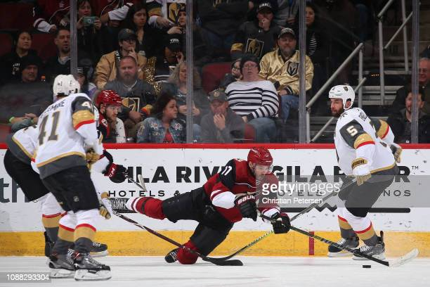 Alex Galchenyuk of the Arizona Coyotes falls as he attempts to control the puck ahead of Deryk Engelland of the Vegas Golden Knights during the...