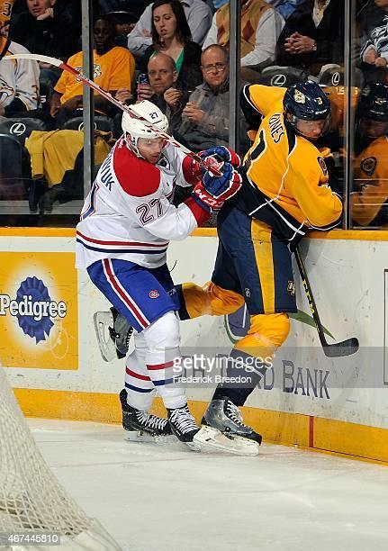 Alex Galchenyuk of the Montreal Canadiens checks Seth Jones of the Nashville Predators into the boards during the second period at Bridgestone Arena...