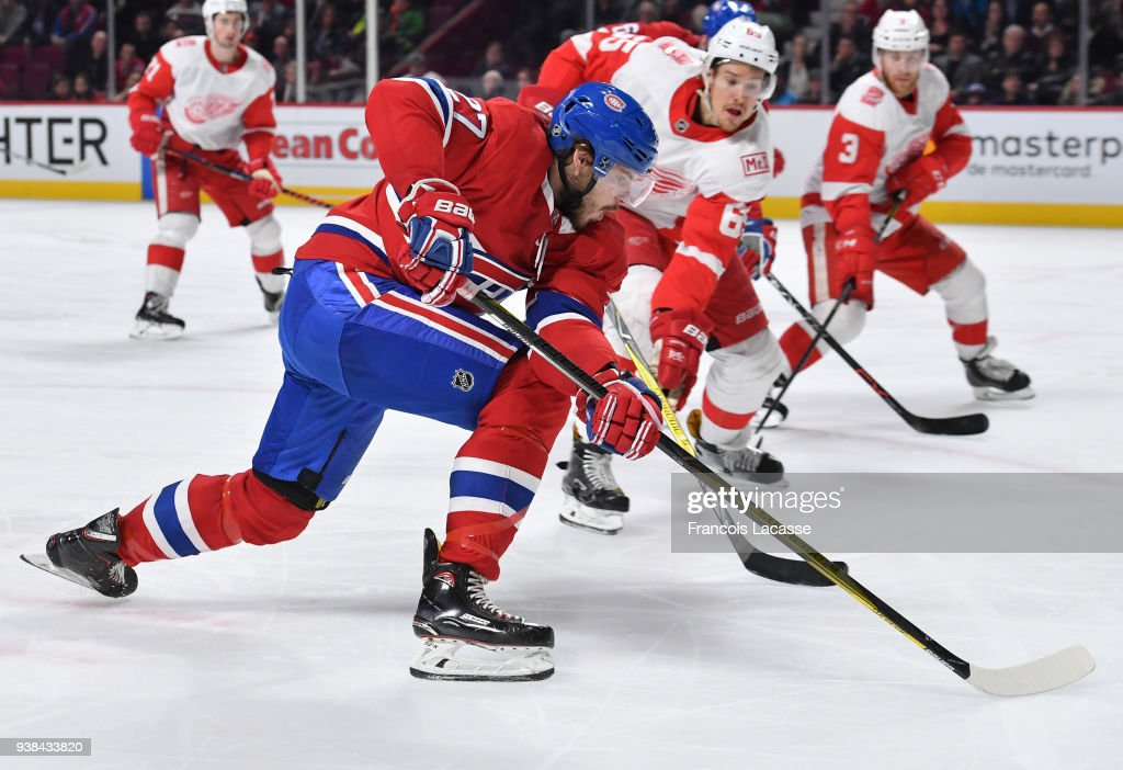 Alex Galchenyuk #27 of the Montreal Canadiens passes the puck against pressure from Danny DeKeyser #65 of the Detroit Red Wings in the NHL game at the Bell Centre on March 26, 2018 in Montreal, Quebec, Canada.