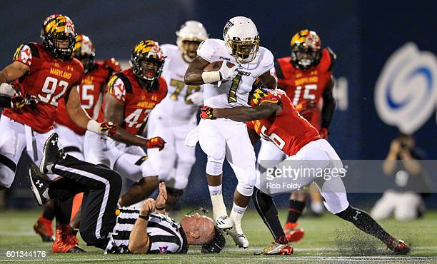 Alex Gardner of the FIU Panthers knocks over an official as he is hit by Milan Barry-Pollock of the Maryland Terrapins at FIU Stadium on September 9,...