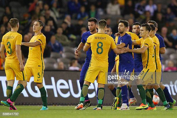 Alex Gersbach of the Socceroos is held back by teammate Mark Milligan as Greece players confront Bailey Wright of the Socceroos after a contest...
