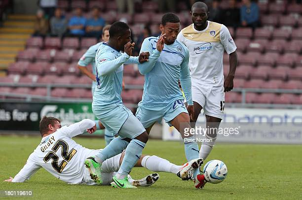 Alex Gilbey of Colchester United challenges for the ball with Franck Moussa and Jordan Clarke of Coventry City during the Sky Bet League One match...