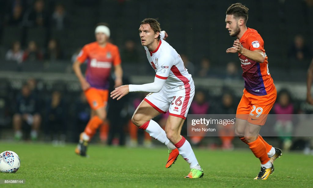 Alex Gilbey of Milton Keynes Dons moves forward with the ball away from Matt Grimes of Northampton Town during the Sky Bet League One match between Milton Keynes Dons and Northampton Town at StadiumMK on September 26, 2017 in Milton Keynes, England.