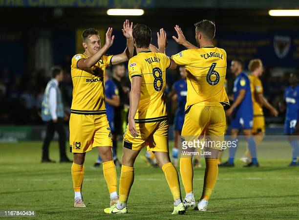 Alex Gilbey of MK Dons is congratulated after scoring the winning penalty during the Carabao Cup First Round match between AFC Wimbledon and Milton...