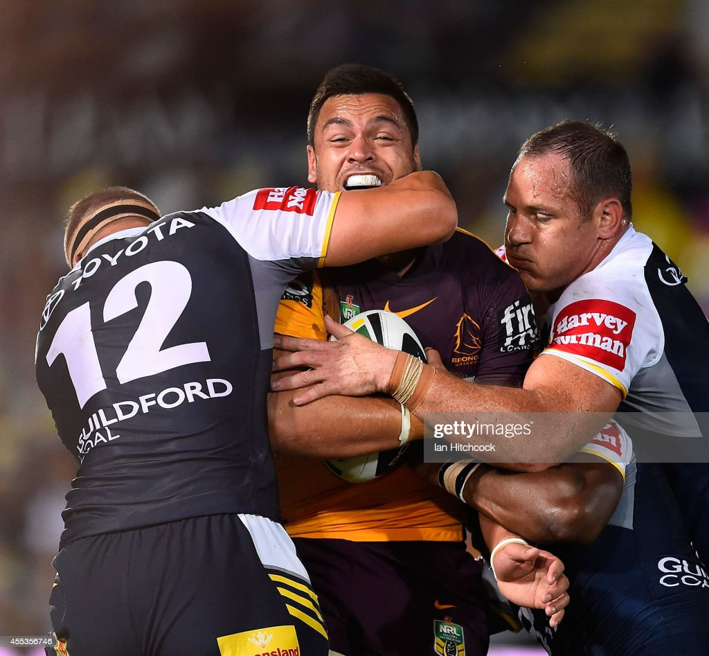 Alex Glenn of the Broncos is tackled by Matthew Scott and Tariq Sims of the Cowboys during the NRL 1st Elimination Final match between the North Queensland Cowboys and the Brisbane Broncos at 1300SMILES Stadium on September 13, 2014 in Townsville, Australia.