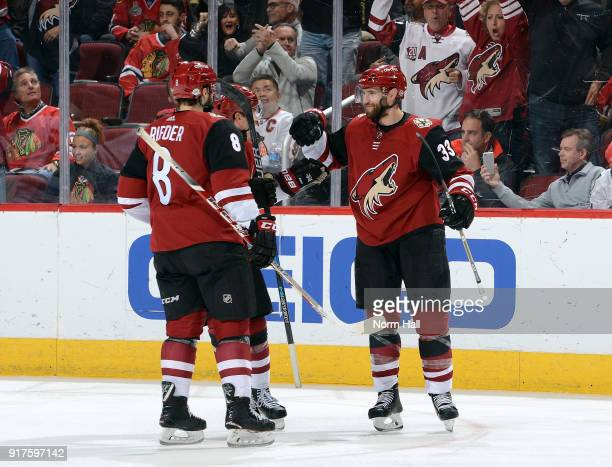 Alex Goligoski and Tobias Rieder of the Arizona Coyotes congratulate teammate Nick Cousins after Cousins' third period goal against the Chicago...