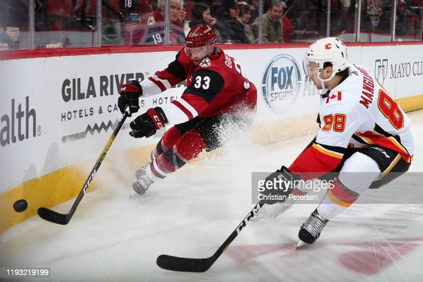 Alex Goligoski of the Arizona Coyotes attempts to play the puck under pressure from Andrew Mangiapane of the Calgary Flames during the second period...