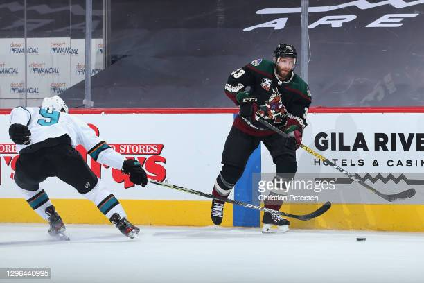 Alex Goligoski of the Arizona Coyotes controls the puck ahead of Evander Kane of the San Jose Sharks during the third period of the NHL game at Gila...