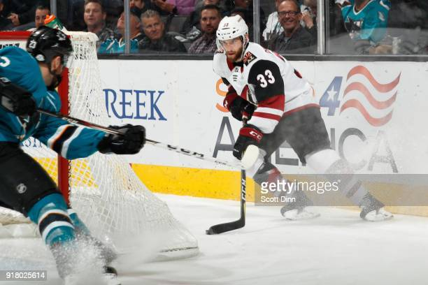 Alex Goligoski of the Arizona Coyotes keeps the puck away from Barclay Goodrow of the San Jose Sharks at SAP Center on February 13 2018 in San Jose...