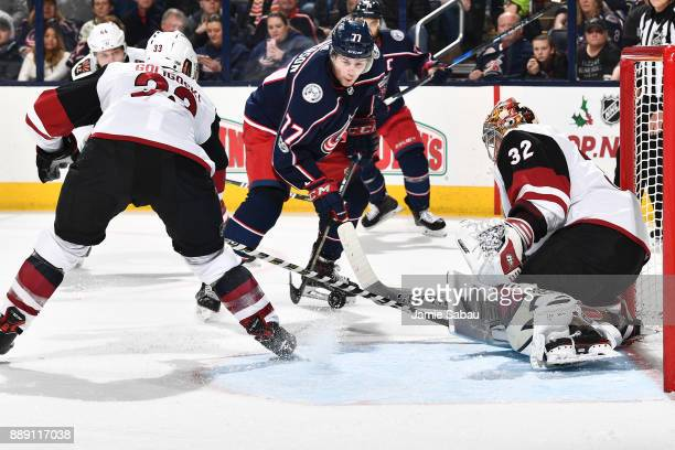 Alex Goligoski of the Arizona Coyotes reaches in to clear the puck as Antti Raanta of the Arizona Coyotes stops a shot on Josh Anderson of the...