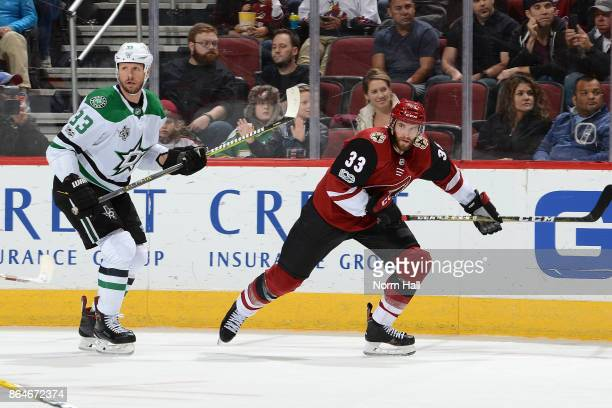 Alex Goligoski of the Arizona Coyotes skates after the puck against Marc Methot of the Dallas Stars at Gila River Arena on October 19 2017 in...
