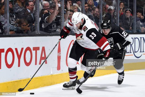 Alex Goligoski of the Arizona Coyotes skates with the puck against Dustin Brown of the Los Angeles Kings during the game on March 29 2018 at Staples...