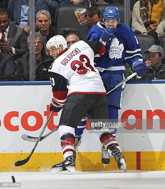 Alex Goligoski of the Arizona Coyotes squeezes Mitchell Marner of the Toronto Maple Leafs off the puck during an NHL game at the Air Canada Centre on...