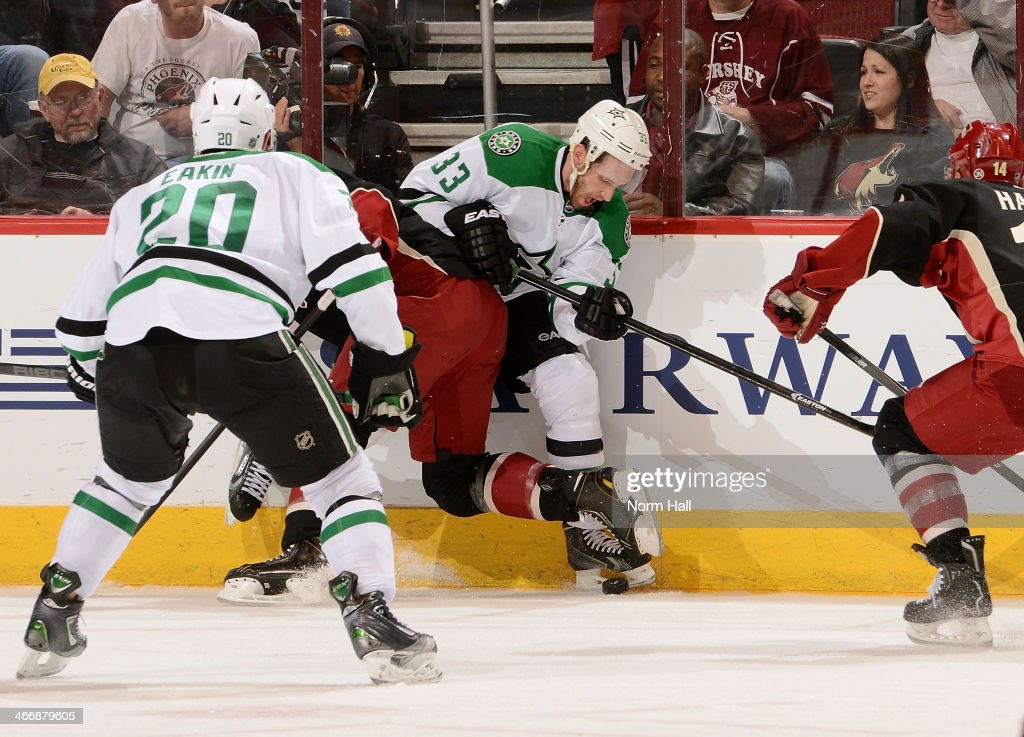 Alex Goligoski #33 of the Dallas Stars is checked into the boards by a Phoenix Coyotes player during the third at Jobing.com Arena on February 4, 2014 in Glendale, Arizona.