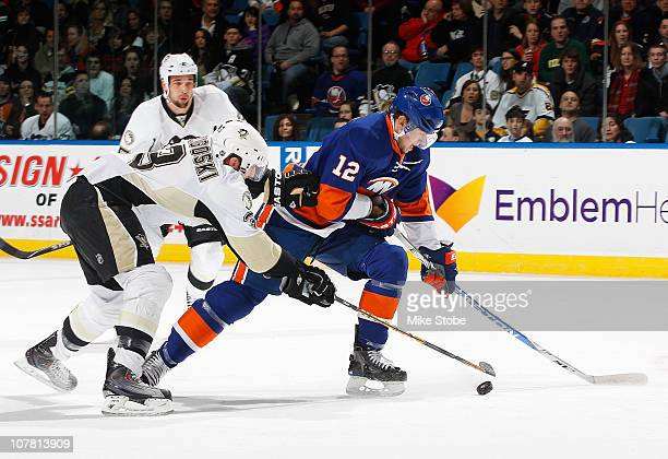 Alex Goligoski of the Pittsburgh Penguins battles for the puck against Josh Bailey of the New York Islanders on December 29, 2010 at Nassau Coliseum...