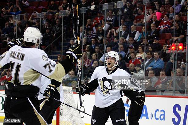 Alex Goligoski of the Pittsburgh Penguins celebrates his third period goal with team mate Evgeni Malkin during the NHL game against the Montreal...