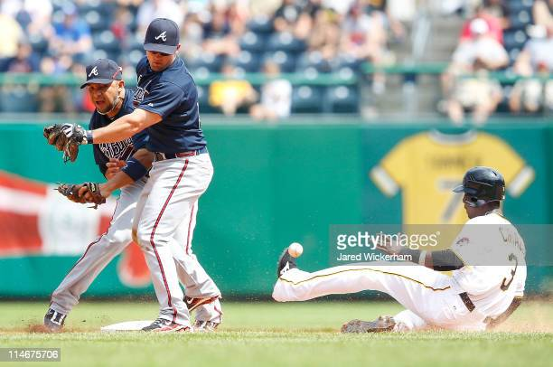 Alex Gonzalez and Dan Uggla of the Atlanta Braves collide when trying to both make a play at second base in front of Pedro Ciriaco of the Pittsburgh...