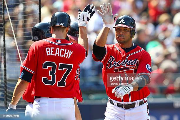 Alex Gonzalez of the Atlanta Braves celebrates with Brandon Beachy after a solo home run in the fourth inning of the game against the New York Mets...