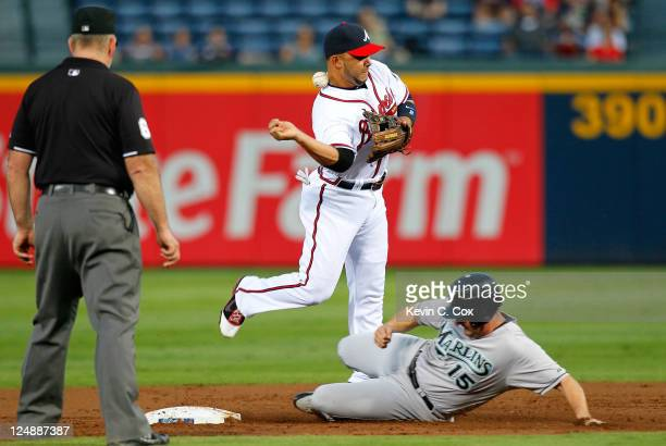 Alex Gonzalez of the Atlanta Braves loses the ball as he attempts to turn a double play over Gaby Sanchez of the Florida Marlins in the second inning...