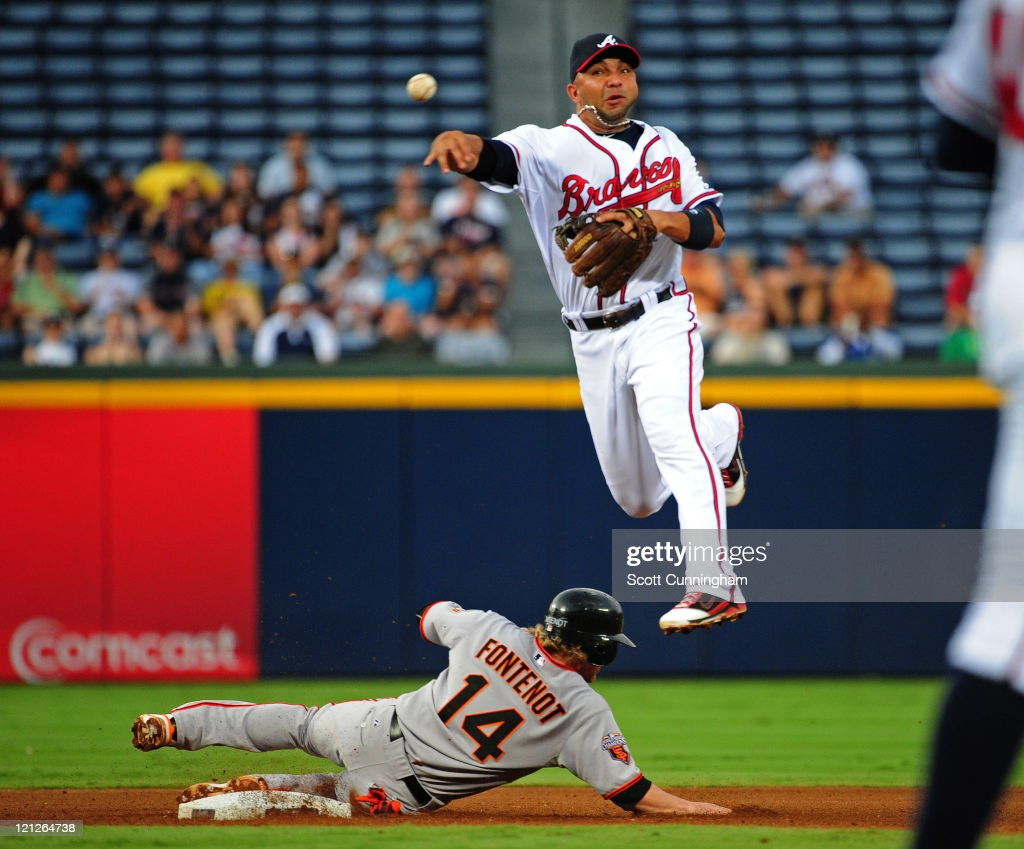Alex Gonzalez #2 of the Atlanta Braves turns a double play against Mike Fontenot #14 of the San Francisco Giants at Turner Field on August 16, 2011 in Atlanta, Georgia.