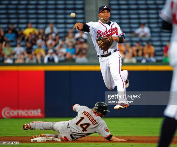 Alex Gonzalez of the Atlanta Braves turns a double play against Mike Fontenot of the San Francisco Giants at Turner Field on August 16 2011 in...